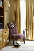 Dainty chair with violet upholstery and high-heeled shoes in corner