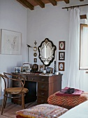 Antique desk with drawers and curved wood armchair in corner of bedroom