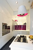 Kitchen with white cupboard doors and designer pendant lamp above gas hob in kitchen island