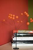 Metallfuss mit Kugelstrauss im 70er Jahre Stil neben Bücherstapel vor rot getönter Wand