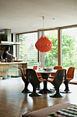 Brown plastic shell chairs with orange cushions in dining area below orange pendant lamp
