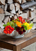 Colourful flower arrangement of nasturtiums, dill and French marigolds in old jelly mould on wooden table