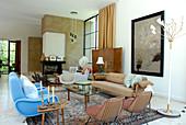 Verschiedene Stühle im Stilmix und mehrarmige Stehleuchte in grosszügigem Wohnzimmer eines klassisch modernen Wohnhauses