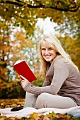 Young woman reading book on blanket in garden with autumnal foliage