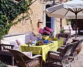 Sommerlich gedeckter Tisch mit Rattansesseln im Freien
