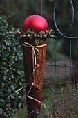 Rusty cone topped with large, red bauble framed with a wreath of thuja twigs and bells