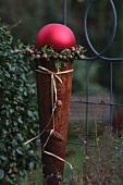 Rosttüte mit grosser roter Kugel gefüllt, umrahmt von Thujakränzchen mit Glöckchen
