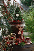 Old wooden barrel decorated with miniature Christmas tree, ivy, apples, Father Christmas figure and lantern