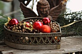 Heart-shaped basket filled with pine cones and baubles in front of iron angel figure
