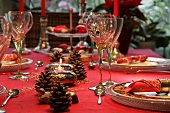 Table set and decorated in red for Christmas with pine cones and silver fern fronds