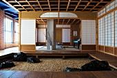Vorraum mit Podest und gekiestem Boden vor offenem Meditationsraum mit japanischen Wänden in Industriehalle
