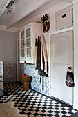 A country house bathroom with black and white floor tiles and old Delft wall tiles