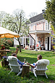 A couple sitting on wooden armchairs covered with sheep skins drinking wine in the garden of a historic Dutch country house