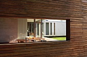 Window aperture in modern wooden facade with view of terrace table in front of contemporary house