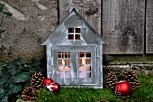 Festive garden decoration: little zinc cottage with candles on bed of moss