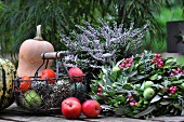 Autumnal table decoration with ornamental gourds, heather, crab apples and olive wreath