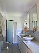 Designer Bad mit zwei Waschschüsseln auf dem Waschtisch und Glastür vor Duschbereich