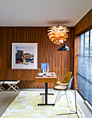 Desk with two chairs in front of large window in wood-panelled office
