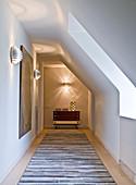 Wandleuchten, Gemälde, Wandkonsole und Teppich auf dem Gang im Dachgeschoss