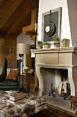 Sitting area with antiques in front of an fireplace with an old stone surround in a renovated country home