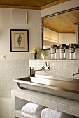 Antique accessories for a steel trough and white mosaic tiles in a modern bathroom