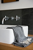 Small towels in shades of grey on wooden washstand with modern countertop washbasin