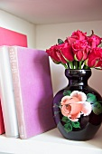 Bouquet of red roses in an old-fashioned ceramic vase decorated with roses next to book in a bookshelf