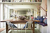 Second-hand chic - old dining table with crystal candelabras in front of a large mirror with retro metal chairs and colorful pillows