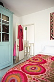 Feminine bedroom with a jazzy, colorful bedspread, dressing gown with red hearts and blue pastel country style cupboard