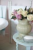 Rosenstrauss in altmodischer Vase auf antikem Bad-Tischchen