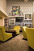 Groups of armchairs with yellow upholstery in lounge with ornate, retro-style black and white wallpaper