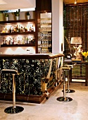Illuminated bar clad with animal skin print and chrome bar stools