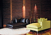 Black and lime green chaise longue in front of a wall hung with dark reed mats