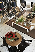 Open living room with a animal skin rug and black chandelier; underneath a large bouquet of roses on a round table