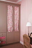 Clothes closet with door drapes - their color enhances the striped pattern of the wallpaper