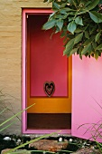 View from outside through a bright violet door of a pink and orange wall niche with an animal head inside a stylized heart