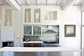 Tisch vor Wand mit gemauerten Regalöffnungen und Mini Küchenzeile