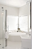 Elegant designer bathroom with corner bath tub in front of a window and closed blinds