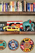 Books and tin toys on wooden shelves and painted plates hung on the wall below