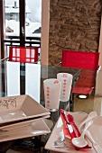 Glastisch mit Essgeschirr und Gläsern vor rustikaler Natursteinwand; im Hintergrund verschneite Berghäuser