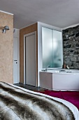 Bedroom with corner bathtub against stone wall; toilet and sink behind frosted glass wall