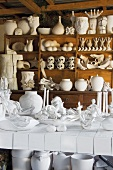Collection of porcelain on a rustic wall shelf unit a white tile table