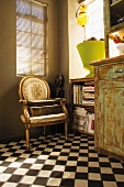 Corner with kitchen buffet in the shabby look, book shelves and a gilt baroque chair