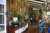 Blooming veranda with a solid wood sideboard, a collection of blue vases and plants in terra cotta pots
