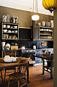 Olive green kitchen with antique furniture, art noveau ceiling lamp and a collection of black and white vases on the kitchen shelves