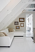 Elegant white sofa and framed photos on wall below open attic roof structure