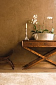 Orchids in metal bowl on antique console table against mottled grey wall