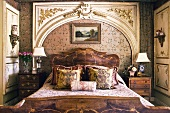 Pile of cushions on bed with antique wooden frame in front of Rococo wall panel in the shape of a portal