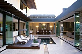 A U-shaped living area - opening into a courtyard with a pond and loungers on a wooden deck
