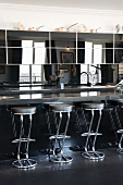 Round tube chrome bar stools at a modern kitchen counter with reflective top units